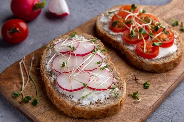 Sandwiches mit radieschen, kirschtomaten und microgreens nahaufnahme auf einem schneidebrett