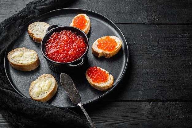 Sandwiches mit rotem fischkaviar, auf schwarzem holztischhintergrund mit kopienraum für text