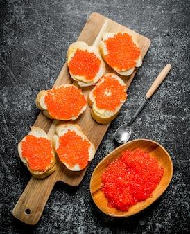 Sandwiches mit rotem kaviar auf einem schneidebrett, rotem kaviar in einer schüssel und einem löffel. auf schwarzem rustikalem hintergrund