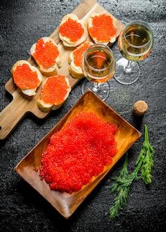 Sandwiches mit rotem kaviar und rotem kaviar auf einem teller mit dem wein. auf schwarzem rustikalem hintergrund