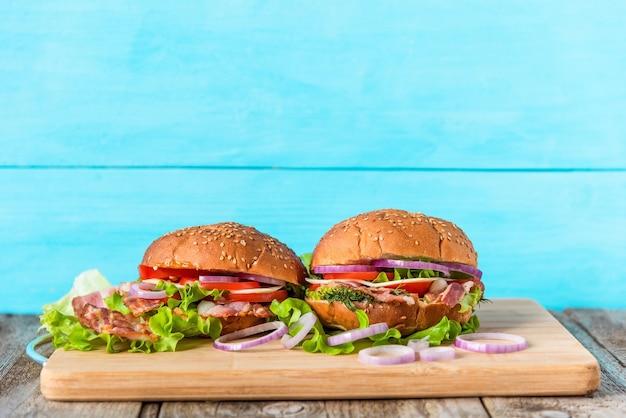 Sandwiches mit salat, speck, zwiebelringen, tomaten, ei, käse und sesambrötchen auf hellblauem hintergrund.