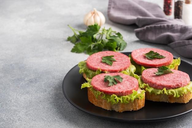 Sandwiches mit salatblättern und geschnittener salamiwurst auf schwarzem teller. platz kopieren