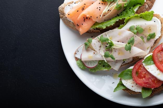 Sandwiches mit schinken, radieschen, romano-salat, baby-basilikum, mascarpone-käse, caprese-salat an einer schwarzen wand.