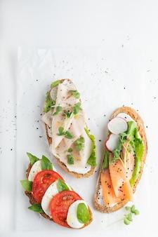 Sandwiches mit schinken, radieschen, romano-salat, baby-basilikum, mascarpone-käse, caprese-salat an einer weißen wand. speicherplatz kopieren. draufsicht.