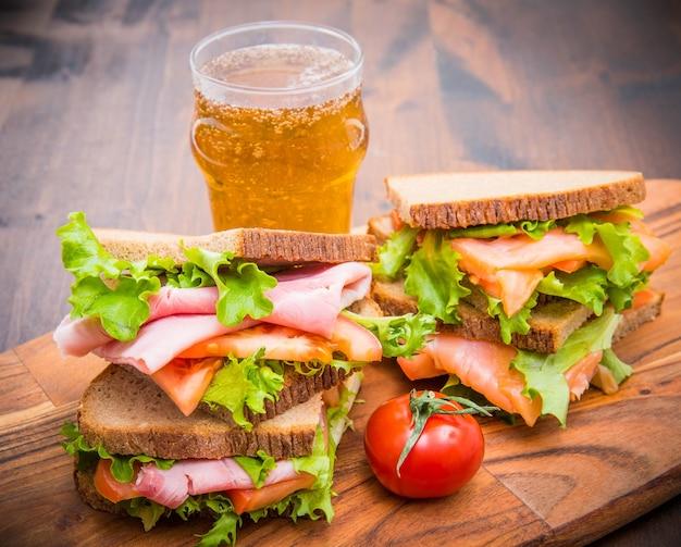 Sandwiches mit schinken und räucherlachs mit biergläsern