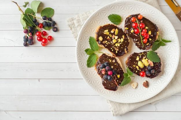 Sandwiches mit schokoladenmasse, pistazien und frischen beeren auf einem teller.