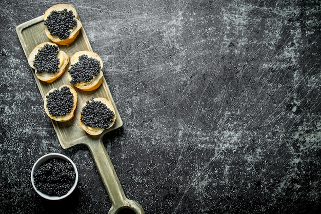 Sandwiches mit schwarzem kaviar auf einem schneidebrett und kaviar in einer schüssel. auf schwarzem rustikalem hintergrund
