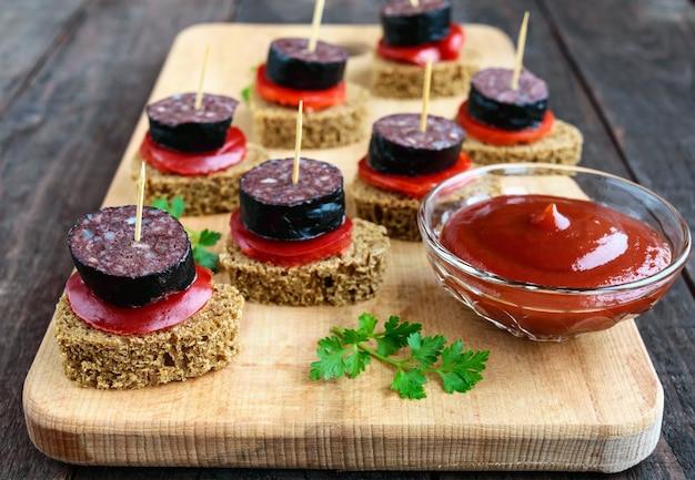 Sandwiches mit schwarzem roggenbrot, blutwurst (morcillo) und paprika am spieß