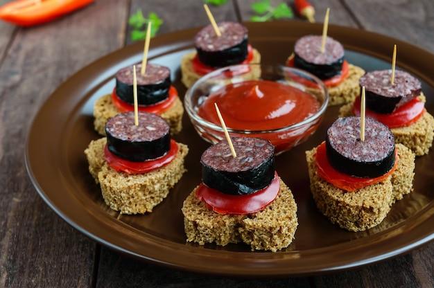 Sandwiches mit schwarzem roggenbrot, blutwurst (morcillo) und paprika