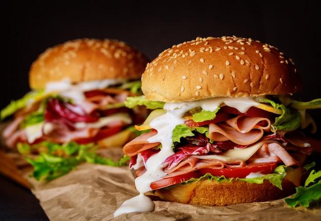 Sandwiches mit sesam mit schinken, salat, käse und tomaten