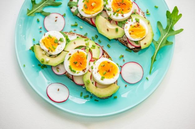 Sandwiches mit weich gekochtem ei, avocado, radieschen, rucola, frühlingszwiebeln und leinsamen auf blauem teller. gesunder snack.