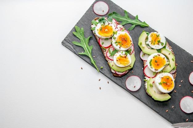Sandwiches mit weich gekochtem ei, avocado, radieschen, rucola, frühlingszwiebeln und leinsamen auf einer schwarzen steinplatte. gesunder snack.