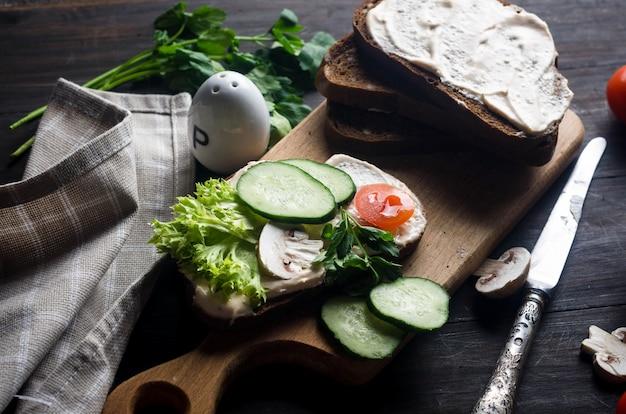 Sandwiches mit weichkäse, salat, gurke, tomaten und pilzen auf einem dunklen holztisch, draufsicht. gesundes frühstück oder mittagessen. flach liegen.