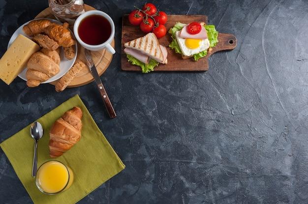 Sandwiches mit würstchen und spiegelei. frühstück mit orangensaft und croissant auf rustikalen holzbrettern.