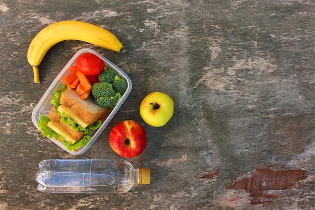Sandwiches, obst und gemüse in der lebensmittelbox, wasser auf altem holztisch. draufsicht. flach liegen.