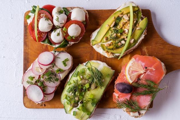 Sandwiches oder tapas mit brot, frischkäse, gemüse und leckeren belägen.