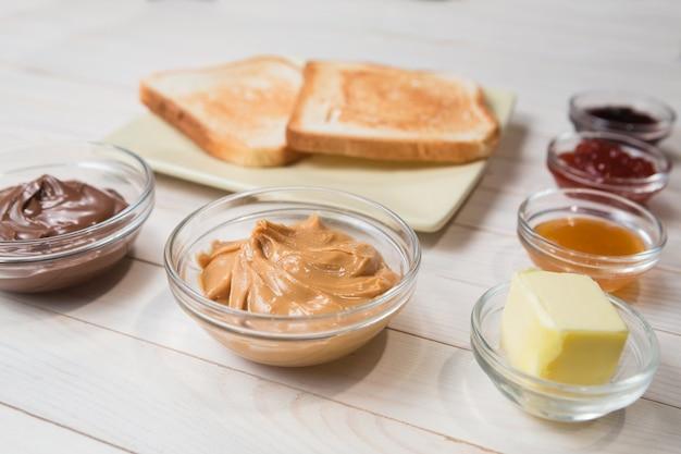 Sandwiches oder toasts mit erdnussbutter, schokoladenpaste und erdbeere, johannisbeere und aprikosengelee oder marmelade auf weißem holztisch