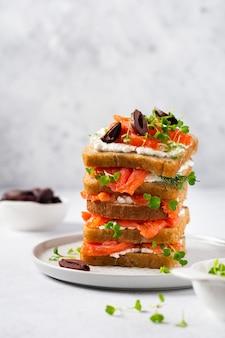 Sandwiches stapeln sich mit geräucherten rosa lachsoliven, kalamata, microgreens und frischkäse auf grauer keramikplatte und trendigem betontisch. traditioneller skandinavischer toast. draufsicht.
