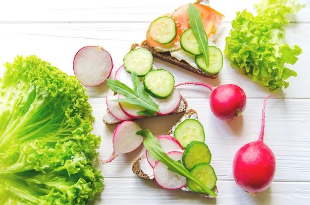 Sandwiches weizen-schwarzbrot mit gurken und rettich mit blättern des frischen grünen salats