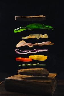 Sandwichfliegen in der luft von speckbrotpfeffergurken und -käse auf einer dunklen nahaufnahme