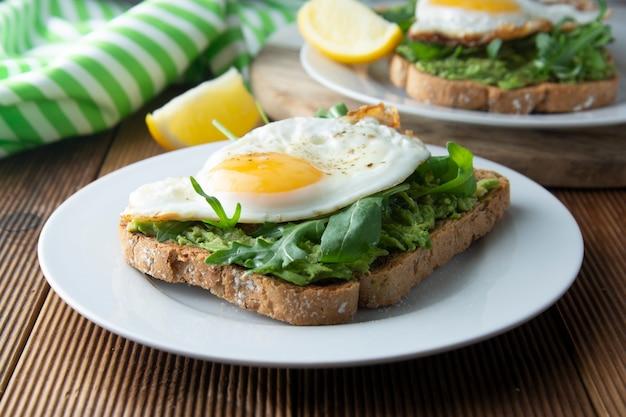Sandwichtoast mit avocado und einem spiegelei auf hölzerner tabelle. gesundes essen.