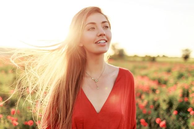 Sanfte blonde langhaarige frau mit perfektem lächeln, das auf mohnfeld im warmen sommersonnenuntergang aufwirft.