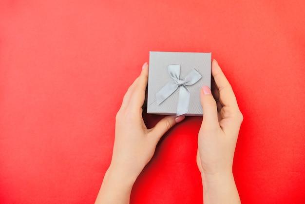 Sanfte hände halten eine kleine geschenkbox auf rotem grund. von oben betrachten. urlaubskonzept, ein geschenk geben. valentinstag oder frauentag.
