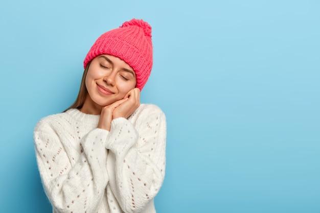 Sanfte junge frau schließt die augen, neigt den kopf, stellt sich etwas angenehmes vor, trägt einen rosa hut, einen winterpullover und posiert vor blauem hintergrund