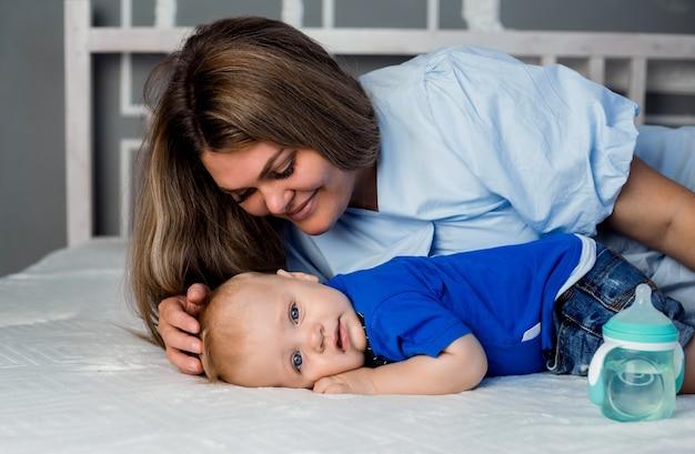 Sanfte mama umarmt einen kleinen jungen auf einem weißen bett