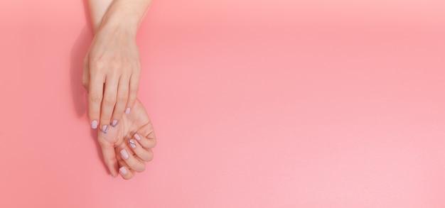 Sanfte nacktmaniküre. weibliche hände auf pastellrosa