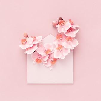 Sanfter orchideenblumenstrauß innerhalb des rosa umschlags als geschenk für frauentag, mütter, valentinstag, geburtstag. flacher hintergrund.