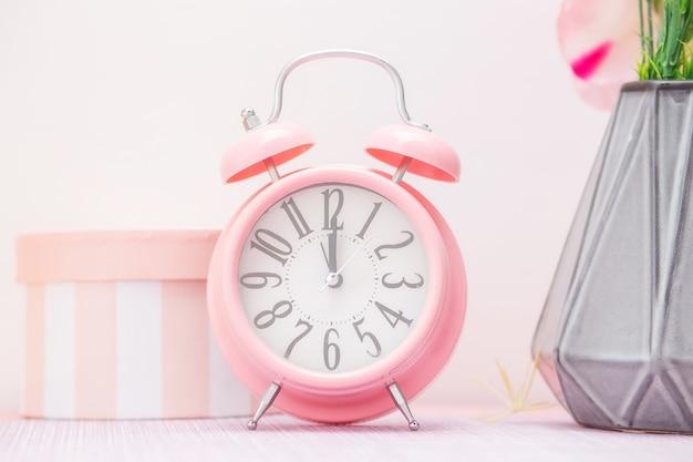 Sanfter rosa wecker neben einer blumenvase und einer dekorativen geschenkbox in einer küche im skandinavischen stil