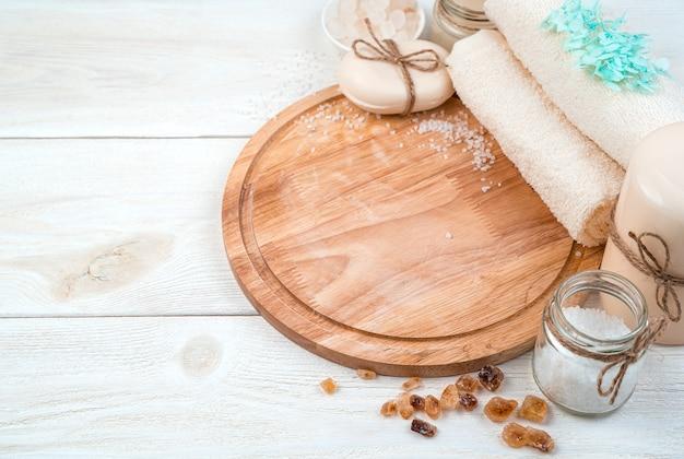 Sanfter spa-hintergrund mit pflegeprodukten auf einem weißen hölzernen hintergrund. seitenansicht. das konzept einer gesunden haut.