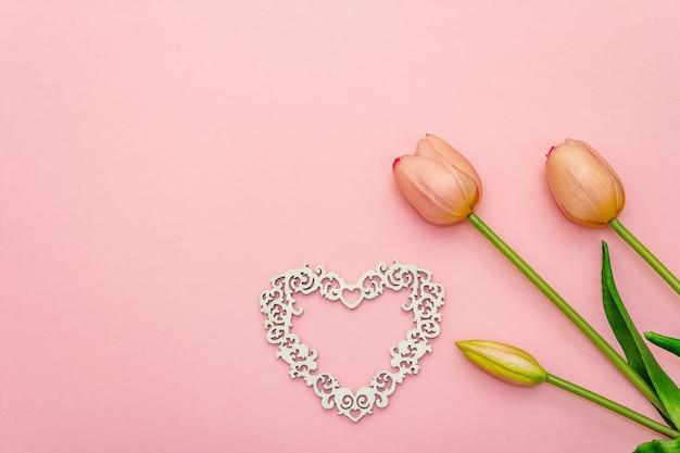 Sanfter strauß der tulpen und des hölzernen durchbrochenen herzens lokalisiert auf hellrosa hintergrund. romantisches konzept des valentinstags oder der hochzeit, kopierraum, flache lage, draufsicht