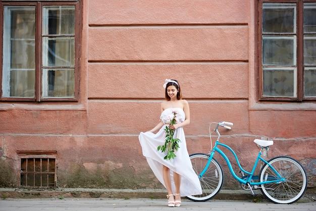Sanftes mädchen sah auf altes gebäude und retro-fahrrad herab