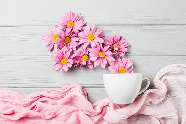 Sanftes stillleben: gerberablumen und weiße tasse