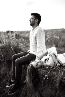 Sanftes und liebevolles paar, das bei sonnenuntergang am ufer sitzt