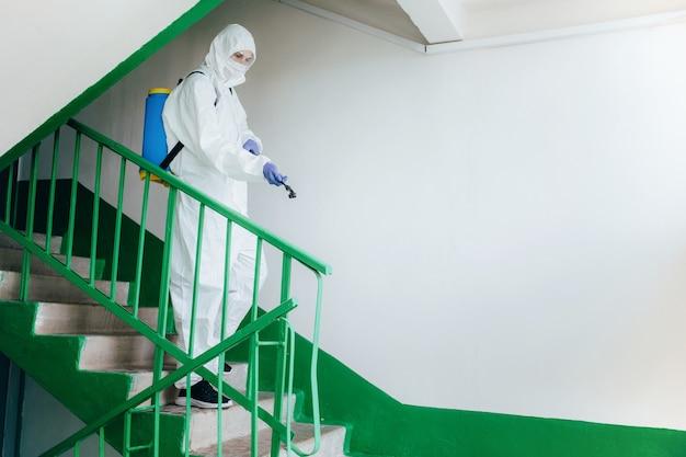 Sanitärfachmann im schutzanzug desinfiziert einen wohnblock im treppenhaus. maßnahmen zur vorbeugung von coronaviren in wohngebieten.