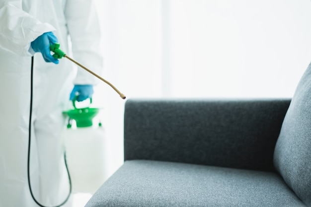 Sanitärpersonal, das eine oberfläche im gebäude desinfiziert, verursacht eine coronavirus- oder covid-19-krankheitspandemie. reinigungskraft mit einem chemischen reinigungsspray auf der oberfläche, um das covid19-virus zu desinfizieren.