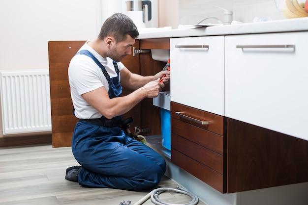 Sanitärtechniker, der an küche arbeitet