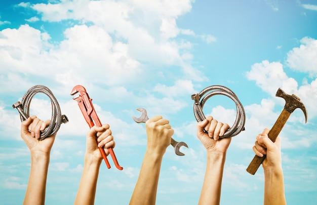 Sanitärwerkzeuge in den händen auf himmelhintergrund mit hauptraumkonzept des kopierraums
