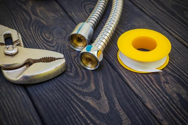 Sanitärwerkzeuge zum anschließen von wasserschläuchen auf schwarzen holzbrettern