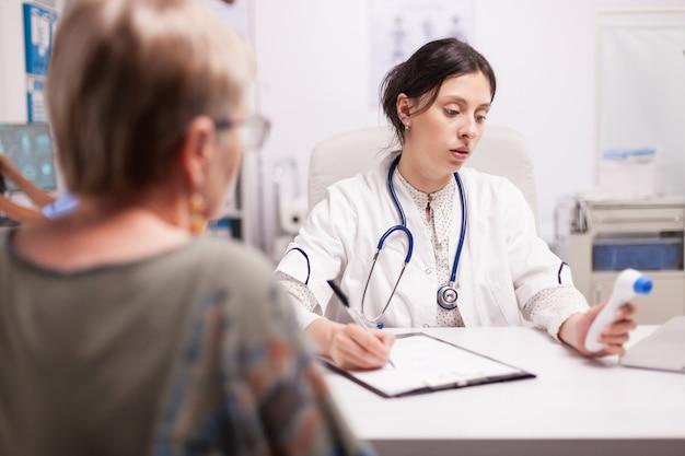 Sanitäter, der die diagnose eines älteren patienten schreibt, nachdem er die körpertemperatur mit einer thermometerpistole im krankenhausbüro gemessen hat. arzt mit stethoskop im weißen kittel.