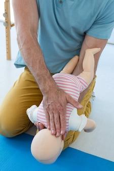Sanitäter, der die wiederbelebung an einer säuglingspuppe demonstriert