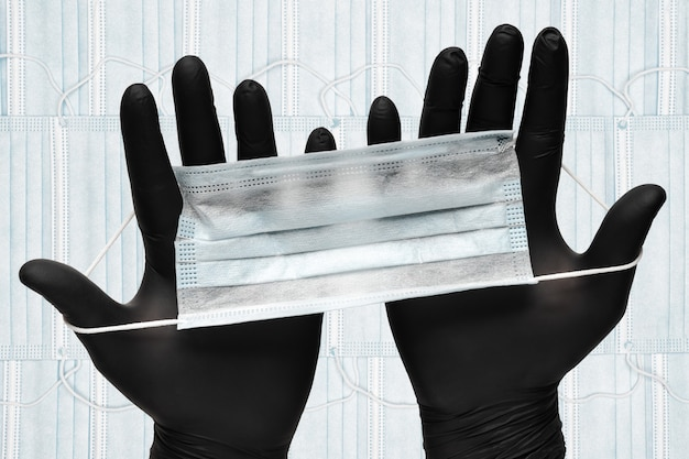 Sanitäter, der eine schützende gesichtsmaske in zwei schwarzen medizinischen handschuhen in den händen auf dem hintergrund von vielen atembandagen für das menschliche gesicht mit gummiohrbändern hält. hygiene- und gesundheitskonzept.