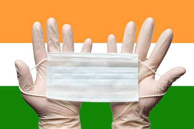 Sanitäter, der gesichtsmaske in zwei händen in weißen medizinischen handschuhen auf der hintergrundflagge indiens hält. konzept coronavirus quarantäne, pandemieausbruch, grippe, hygiene. medizinischer atemverband für das gesicht.