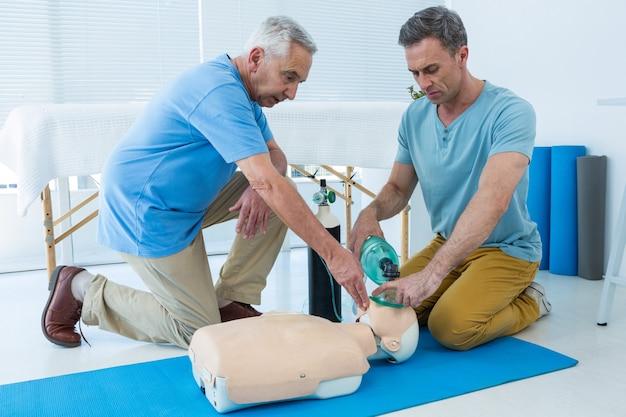 Sanitäter, die eine kardiopulmonale wiederbelebung an einer puppe üben