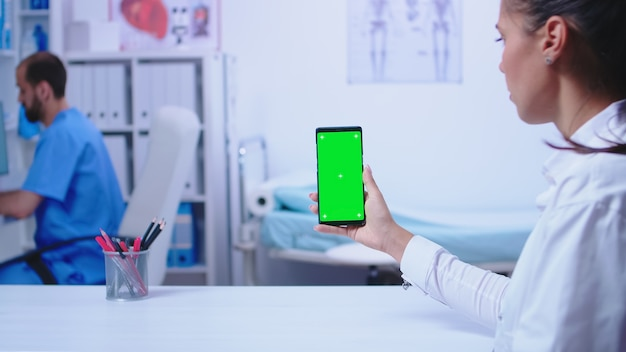 Sanitäter im weißen kittel, der smartphone mit grünem bildschirm im krankenhausschrank hält. krankenschwester, die medizinische blaue uniform trägt.