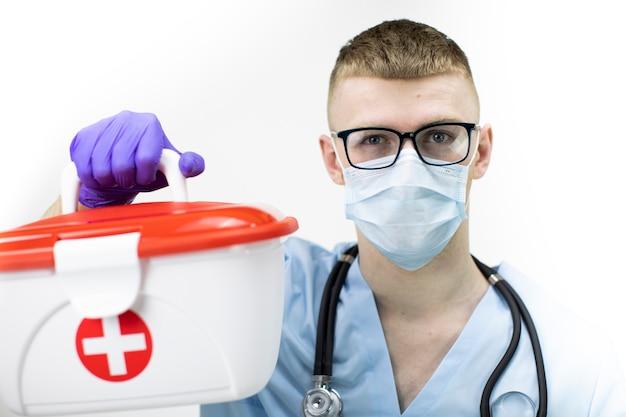 Sanitäter in schutzmaske, brille und blauen latexhandschuhen hält medizinischen fall