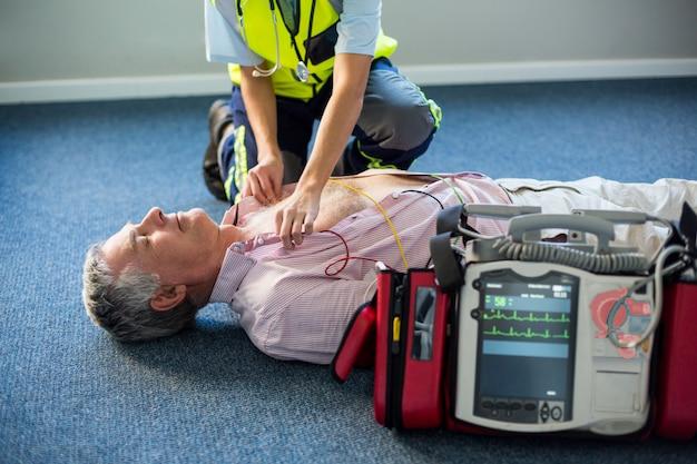 Sanitäter mit einem externen defibrillator bei einem bewusstlosen patienten